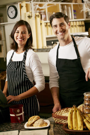 woman shop: Man And Woman Working In Coffee Shop Stock Photo