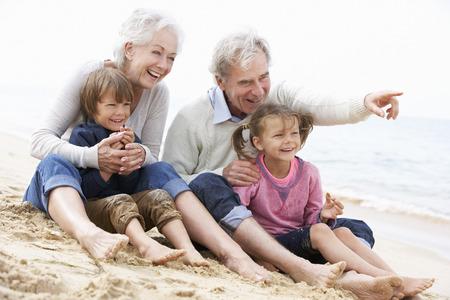 Grootouders en kleinkinderen zitten op het strand Samen