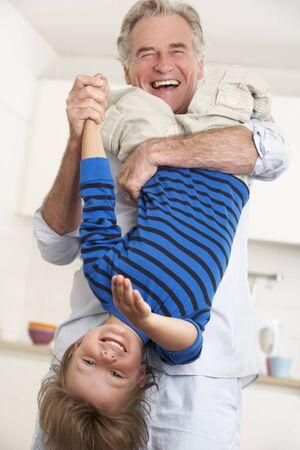 cabeza abajo: Abuelo holding nieto al revés en casa