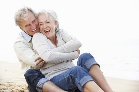 romance: Pares sênior que sentam na praia junto Banco de Imagens