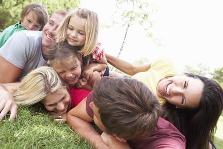 familias unidas: Dos familias que juegan en parque Juntos