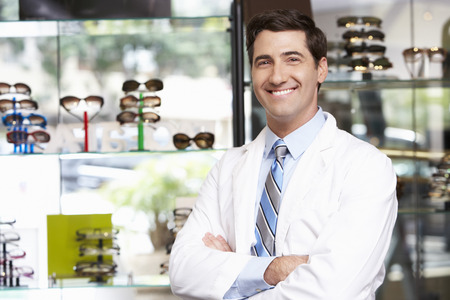 eye care professional: Portrait Of Male Optician By Glasses Display