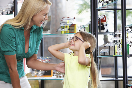 eye exam: Mother And Daughter Choosing Glasses In Opticians Stock Photo