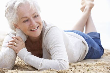 Senior Woman Relaxing On Beach