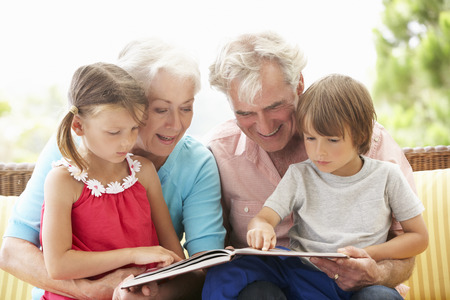 Libro de lectura de abuelos y nietos en el asiento del jardín