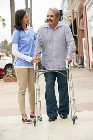 physical impairment: Carer Helping Senior Man To Use Walking Frame Stock Photo