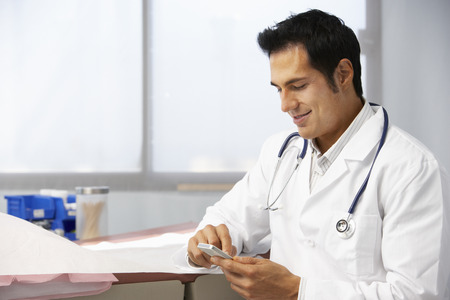 Male Doctor In Surgery Using Mobile Phone Stock Photo