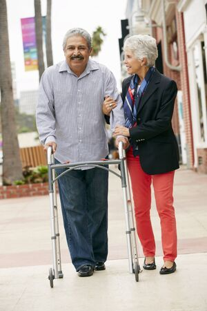 ageing process: Wife Helping Senior Husband To Use Walking Frame