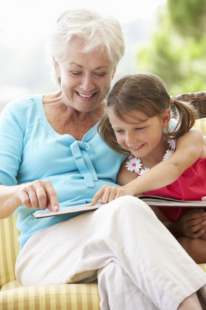 grandparents: Grandmother And Granddaughter Reading Book On Garden Seat