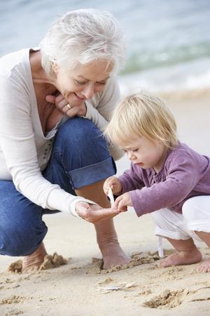 祖母と孫娘のビーチで一緒にシェルを見て