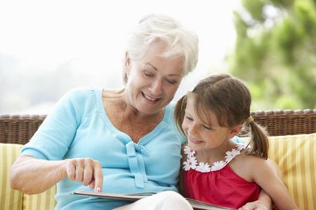 祖母と孫娘庭席で本を読んで