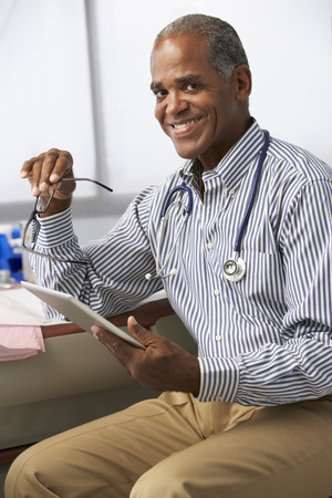 Male Doctor In Surgery Using Digital Tablet Stock Photo