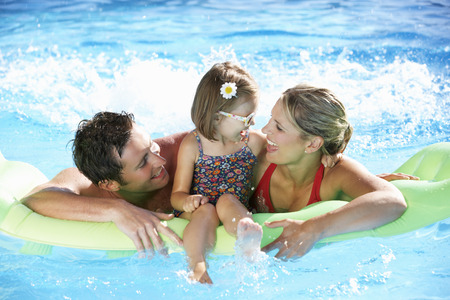 family with three children: Family On Holiday In Swimming Pool Stock Photo