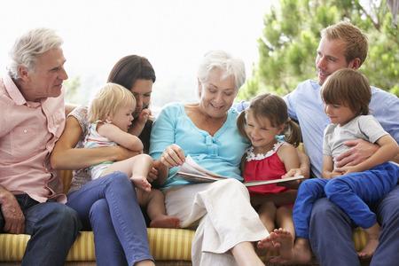 Multi Generation Family Reading Book On Garden Seat