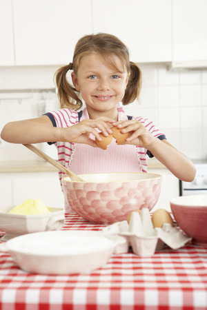cracking: Girl Baking In Kitchen Stock Photo