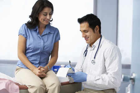 Doctor In Surgery With Female Patient Writing Prescription Stock Photo