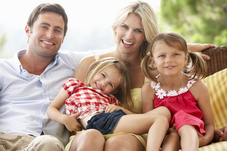 man outdoors: Family Sitting  On Garden Seat Together