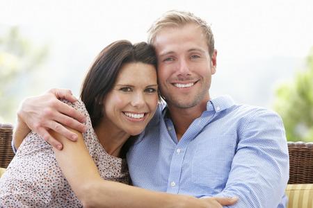pareja abrazada: Pares que se sientan en el asiento al aire libre junto Foto de archivo