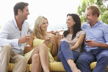 white wine: Group Of Friends Sitting On Outdoor Seat Together