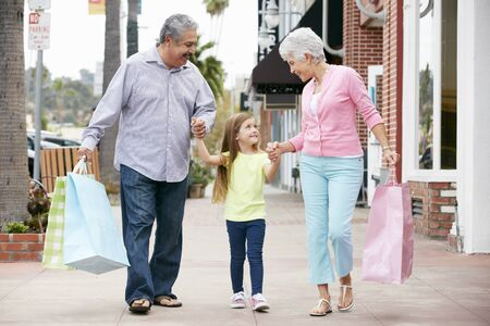 granddaughter: Senior Couple With Granddaughter Carrying Shopping Bags
