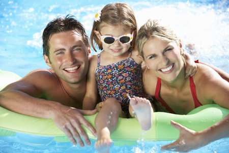 Family On Holiday In Swimming Pool Imagens