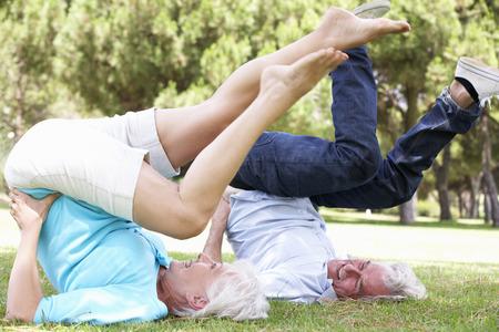 pareja saludable: Pares mayores que ejercitan en jardín junto
