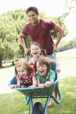 Vader geven kinderen rijden In kruiwagen Stockfoto