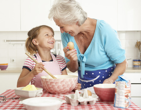 granddaughter: Grandmother And Granddaughter Baking In Kitchen