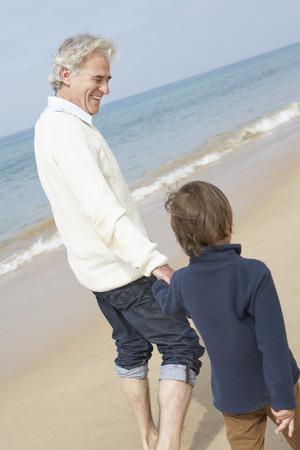 grandson: Grandfather And Grandson Walking Along Beach