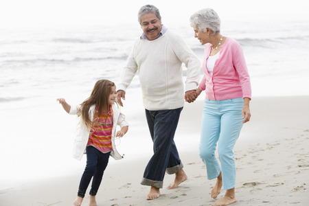 old couple walking: Grandparents Walking Along Beach With Granddaughter