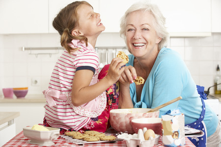 granddaughters: Grandmother And Granddaughter Baking In Kitchen