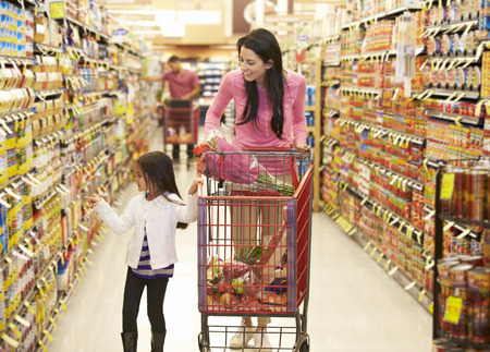 woman shopping cart: Mother And Daughter Walking Down Grocery Aisle In Supermarket
