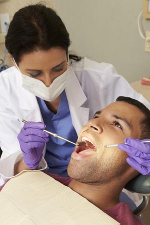 latex glove: Man Having Check Up At Dentists Surgery Stock Photo