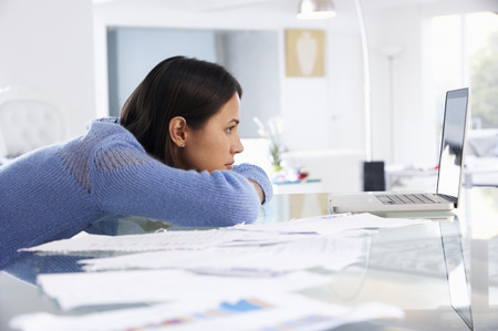 bored woman: Stressed Woman Working At Laptop In Home Office