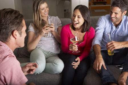 friends drinking: Group Of Friends Sitting On Sofa Talking And Drinking Wine