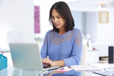 trabajando en casa: Mujer Que Trabaja En La Computadora Port�til En Oficina Principal