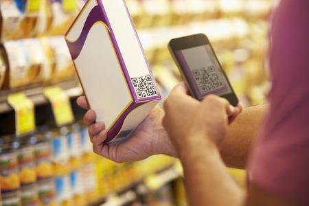 男は携帯電話を持ってスーパーでクーポン コードをスキャン