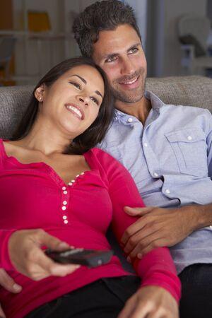 people watching: Hispanic Couple On Sofa Watching TV Together
