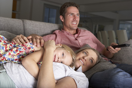 woman on couch: Family On Sofa Watching TV Stock Photo