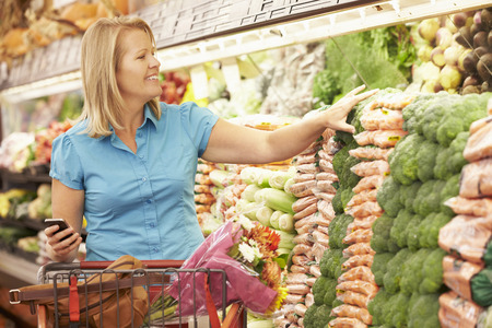 livsstil: Kvinna håller mobiltelefonen I Supermarket Stockfoto