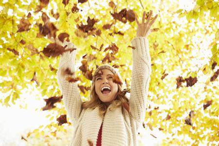 lifestyle: Mujer que lanza las hojas de otoño En El Aire