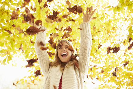 autumn trees: Woman Throwing Autumn Leaves Into The Air