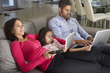 Family On Sofa With Laptop And Digital Tablet Watching TV Foto de archivo