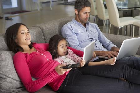 Familie op bank met laptop en digitale tablet-TV kijken
