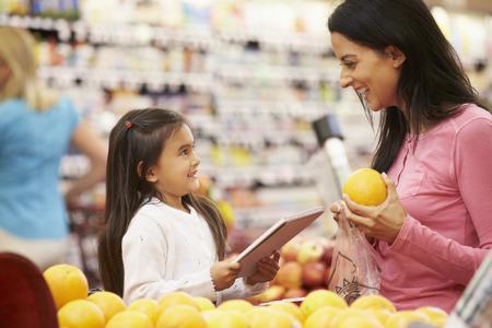tiendas de comida: Madre e hija en el contador de la fruta en supermercado con el Listado