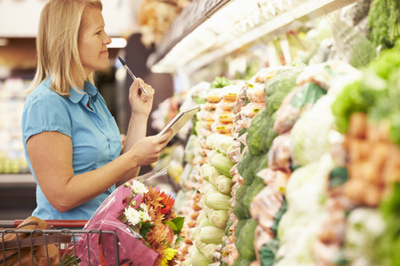 Woman Reading Shopping List In Supermarket Stockfoto