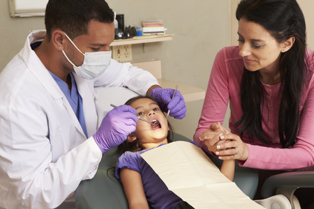 a dentist: Young Girl Having Check Up At Dentists Surgery With Mother