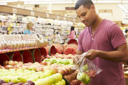 hombre comiendo: Hombre En El Contador fruta en supermercado