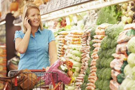 vegetable salad: Woman Talking On Mobile Phone In Supermarket