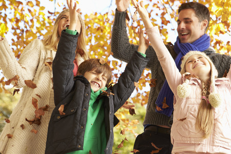 8 year old girl: Family Throwing Leaves In Autumn Garden Stock Photo